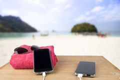 Red tower, sun glasses, mobile charging with power bank over woo Stock Photography