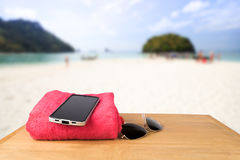 Red tower, sun glasses, mobile charging with power bank over woo Stock Images