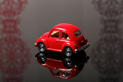 Red toy beetle car. On the table Stock Photos