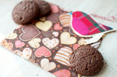 Red toy bird and cookies on dark napkin with image of hearts. Close up. Selective focus royalty free stock image