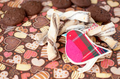 Red toy bird and cookies on dark napkin with image of hearts. Close up. Selective focus stock photography