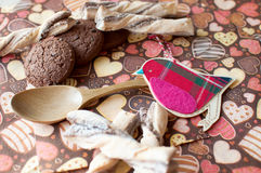 Red toy bird and cookies on dark napkin with image of hearts Royalty Free Stock Images