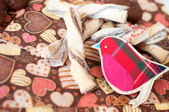 Red toy bird and cookies on dark napkin with image of hearts Stock Image