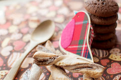 Red toy bird and cookies on dark napkin with image of hearts Stock Images