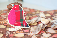 Red toy bird and cookies on dark napkin with image of hearts Stock Photo