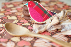 Red toy bird and cookies on dark napkin with image of hearts Royalty Free Stock Photos