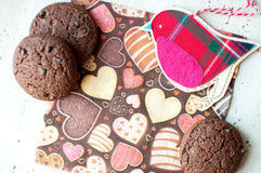 Red toy bird and cookies on dark napkin with image of hearts. Close up. Top view, flat lay stock photos