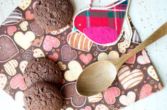 Red toy bird and cookies on dark napkin with image of hearts. Close up. Top view, flat lay royalty free stock images