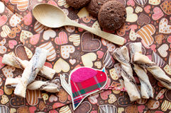 Red toy bird and cookies on dark napkin with image of hearts. Close up. Top view, flat lay royalty free stock photos