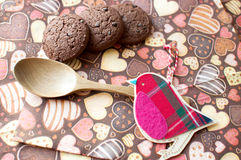 Red toy bird and cookies on dark napkin with image of hearts. Close up. Top view, flat lay stock images
