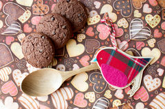 Red toy bird and cookies on dark napkin with image of hearts Royalty Free Stock Image