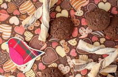 Red toy bird and cookies on dark napkin with image of hearts Stock Photos