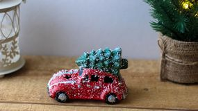 Red toy car carrying Christmas tree on the roof stock photography