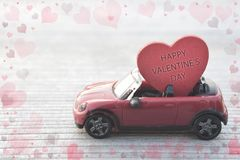 Red toy car delivering Valentine`s day heart royalty free stock photo