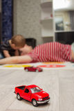 Red toy car, father and son playing at background Stock Photos