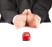 Red toy car in front of businessman, concept for insurance, buying, renting, fuel or service and repair costs Royalty Free Stock Images