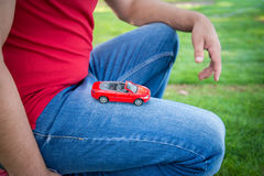 Red toy car on the knee. The man in the red shirt and blue jeans on the green grass Royalty Free Stock Photography