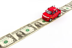 Red toy car on money road. Royalty Free Stock Photos