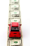 Red toy car on money road. Royalty Free Stock Photo