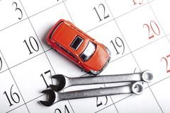 Free Red Toy Car On The Calendar With Dates Next To The Car Are Wrenches Stock Photography - 158539302