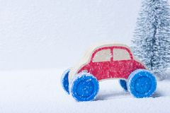 Red Toy Car In A Snowy Scene. Picture of a red toy car driving through a snow storm with a Chistmas tree in the background Stock Images