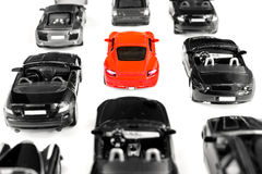 Red toy car standing out from crowd of plenty identical black car Royalty Free Stock Images