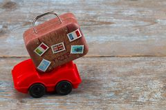 Red toy car with suitcases on a wooden background. Travel concep. T. With copy space Royalty Free Stock Image