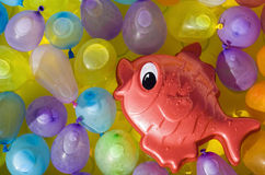 Red toy fish between colored ballons. Red toy fish swimming between colored ballons Royalty Free Stock Photo