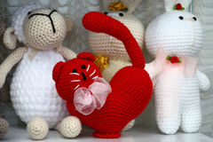 Red toy. In the foreground among other toys there is a figure of a cat made of red threads stock photo