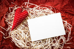 Red toy heart and blank card on straw Royalty Free Stock Image