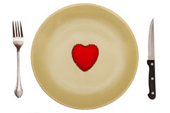 Red, toy heart is on a green plate with cutlery Stock Image