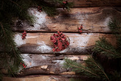 Red toy-heart on wooden planks with spruce branches and red berries all around. Stock Photo