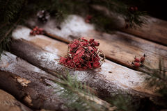 Red toy-heart on wooden planks with spruce branches and red berries all around. Stock Photography