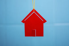 Red toy house. Toy house hanging from a rope on the background wall with blurred background Royalty Free Stock Images