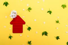 Red toy House, white flowers on a yellow background with green leaves. Real estate business concept, Space for text stock image