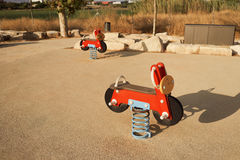Red toy motorcycles in a playground stock photography