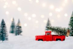 Red toy pickup car carrying Christmas tree. In the snow Stock Photos