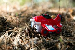 Red toy plane against, a background of foliage royalty free stock images