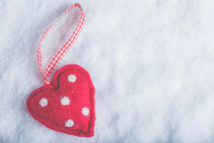 Red toy suave heart on a frosty white snow background. Love and St. Valentine concept. Stock Photos