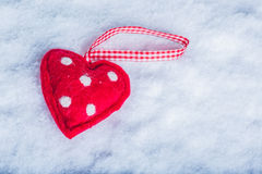 Red toy suave heart on a frosty white snow background. Love and St. Valentine concept. Stock Photography