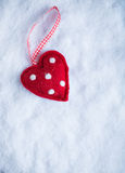 Red toy suave heart on a frosty white snow winter background. Love and St. Valentine concept Stock Image