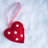 Red toy suave heart on a frosty white snow winter background. Love and St. Valentine concept Stock Photos