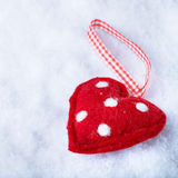 Red toy suave heart on a frosty white snow winter background. Love and St. Valentine concept Stock Images