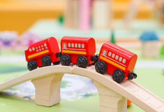 Red toy train. Red wooden toy train crossing the bridge selective focus Stock Photo