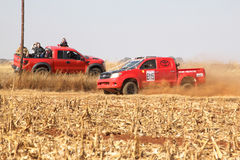 Red Toyota rally truck passing red spectators truck on dusty roa Royalty Free Stock Photo
