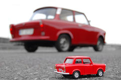 Red Trabant Car Toy. Closeup with real Trabant car in back from ground level Stock Photography