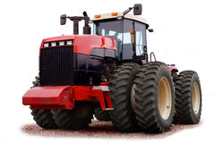 Red tractor. Closeup of modern red wheeled tractor isolated on white background Stock Photos