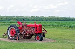 Red Tractor. An old red tractor sits in a field Royalty Free Stock Photography