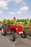 Red tractor. Red learner driver's tractor in a town stock photo