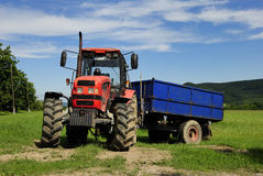 Red tractor. With blue trailer on a grass field Stock Images